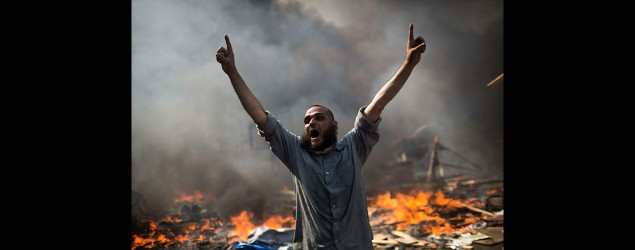 A supporter of ousted Islamist President Mohammed Morsi shouts during clashes with Egyptian security forces in Cairo's Nasr City district, Egypt, Wednesday, Aug. 14, 2013. (AP)
